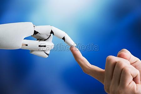 robot touching mans index finger