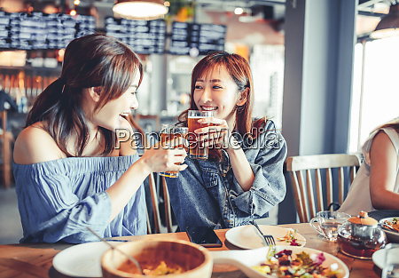 happy young woman with friend dining