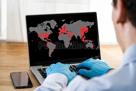 checking coronavirus infection map on laptop