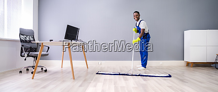 male janitor cleaning floor in office