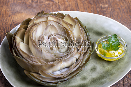 cooked artichoke on a green plate