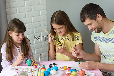 dad with two daughters paint eggs