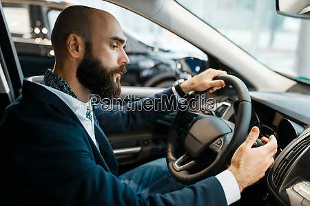 man behind the wheel of automobile