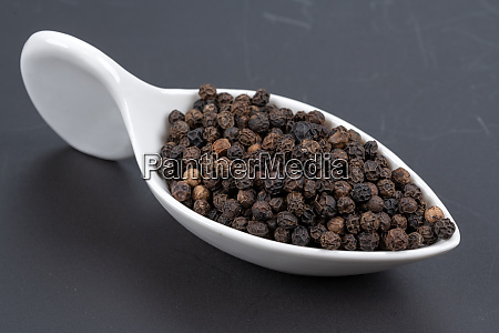 whole black peppercorns in a white