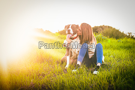 beatiful young woman kissing dog in