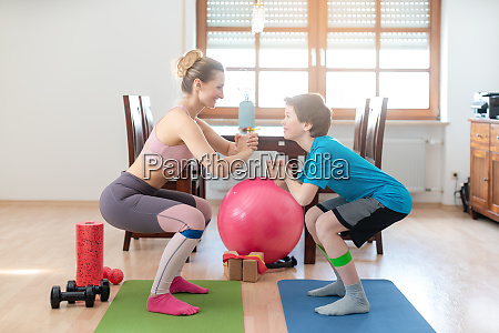 family doing squats on floor at