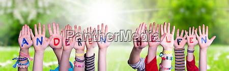 kids hands holding word anderen helfen