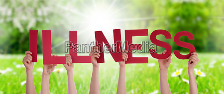 people hands holding word illness grass