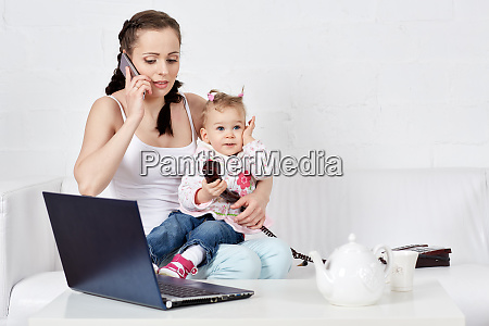 baby and busy mother with notebook