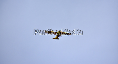 a yellow light aircraft flying in