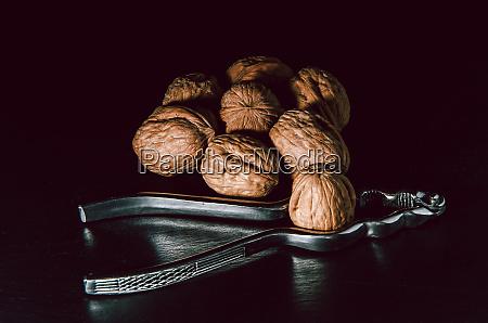 walnuts, with, nutcracker, over, black, background. - 28258494