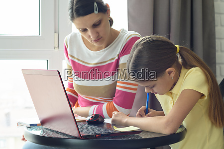 mom helps daughter do homework