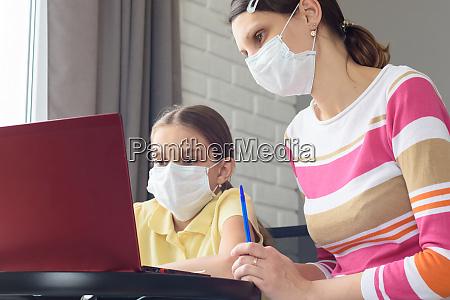 girl and tutor in medical masks