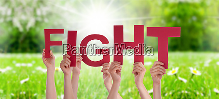 people hands holding word fight grass
