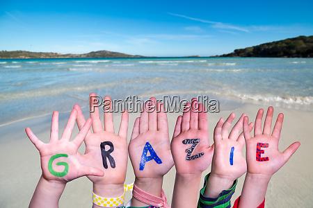 children hands building word grazie means