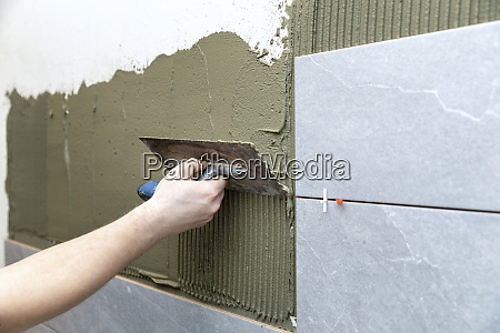 man apply tile adhesive on the