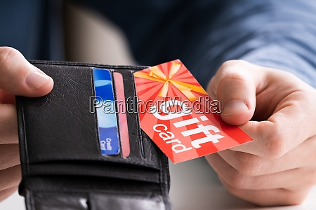 human hand removing gift card from