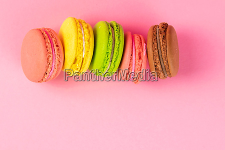 colorful macaroons stand on a pink
