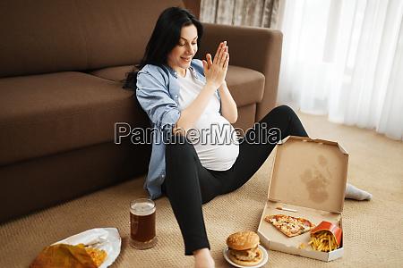pregnant woman smoking and eats unhealthy