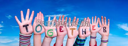 children hands building word together blue