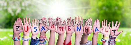kids hands holding word zusammenhalt means