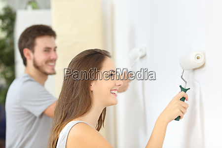 happy couple painting wall with paint