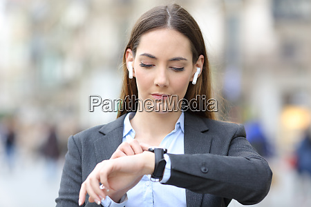 executive, with, earbuds, checking, smart, watch - 28277987