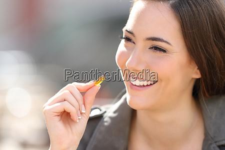 happy, woman, taking, vitamin, pill, outdoor - 28277944
