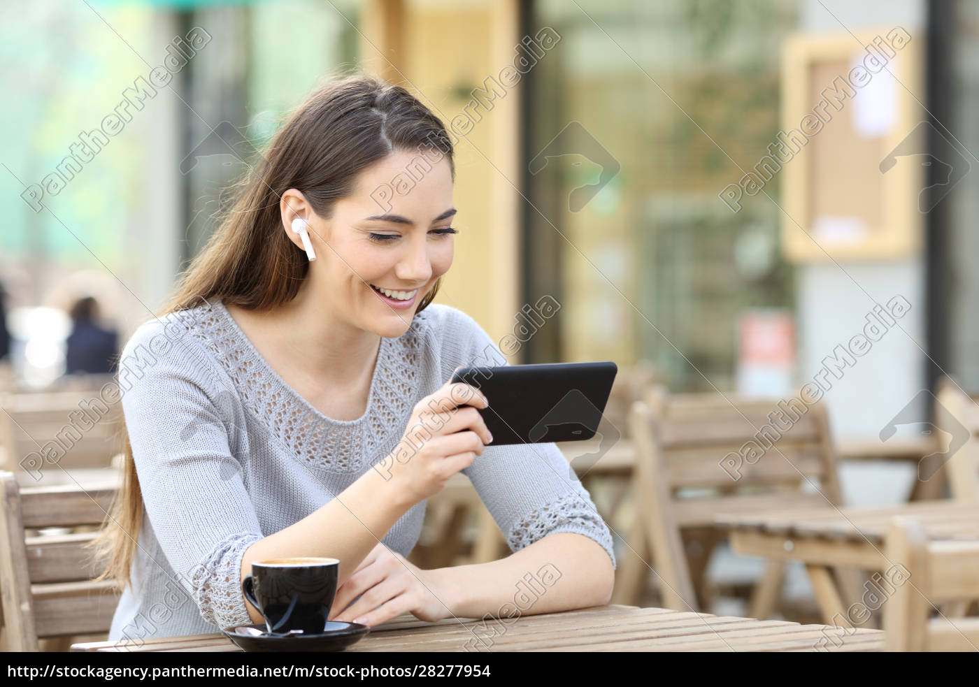 happy, woman, with, earbuds, watching, video - 28277954