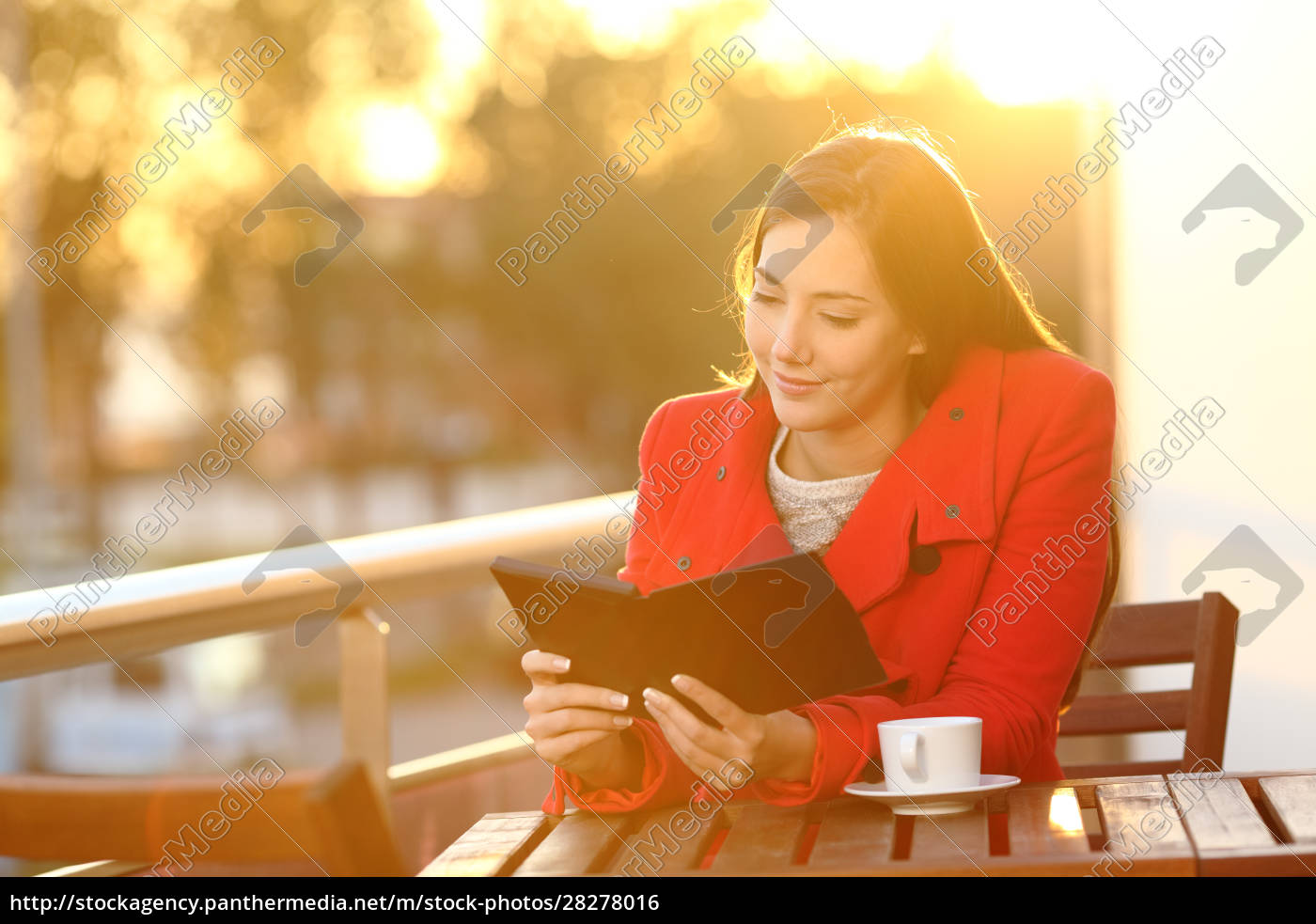 woman, reading, ebook, on, a, balcony - 28278016