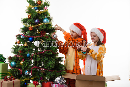 two girls decorate a christmas tree