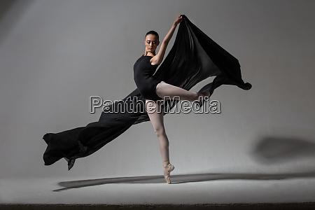 graceful ballerina posing with black cloth