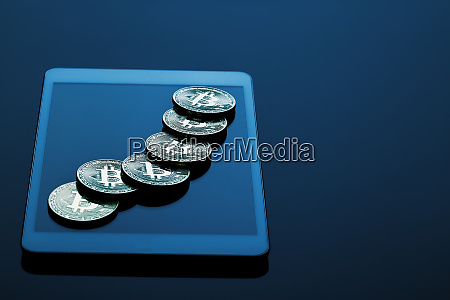 stack of bitcoins on tablet computer