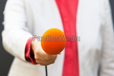 journalist holding microphone making media interview