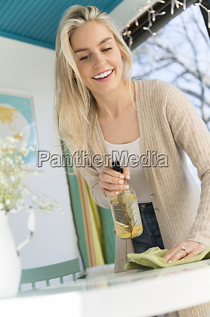 smiling woman cleaning tabletop with natural