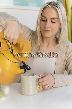 woman making tea pouring water from
