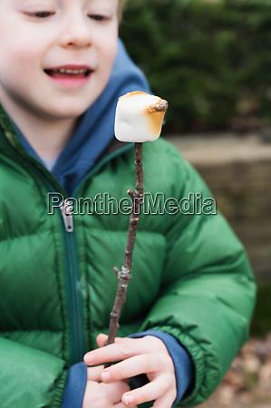boy watching roasted marshmallow on stick