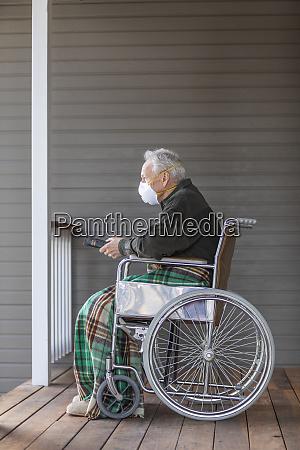 senior man in wheelchair wearing protective