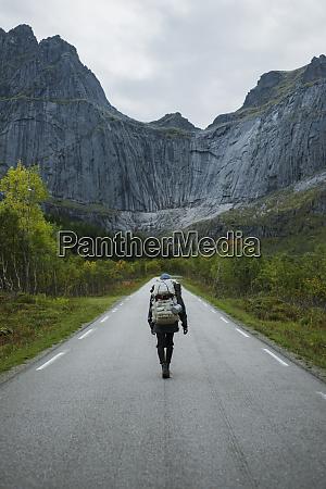 norway lofoten islands backpacker walking down
