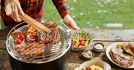 man taking grilled meat off a