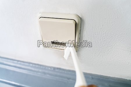 man using tool to press button