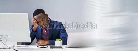 tired african businessman sleeping