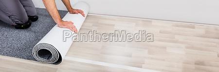 workers hands unrolling carpet on floor