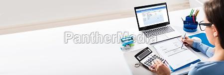 businesswoman calculating invoice using calculator
