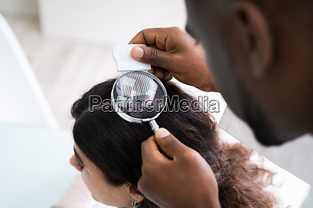 dermatologist checking patients hair with magnifying