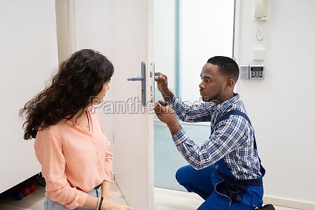 technician fixing the door lock with
