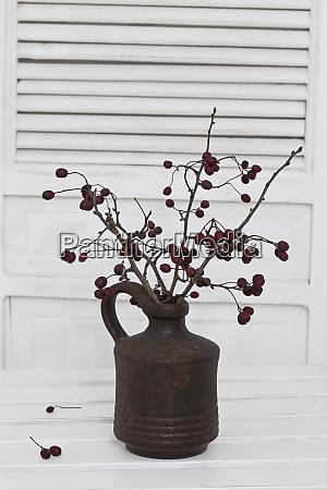 berry twigs in rustic vase