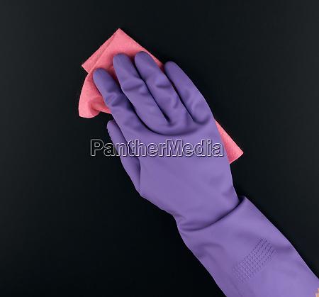 hand holds a pink rag sponge
