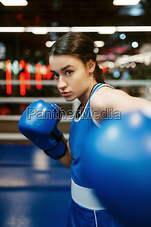 woman in blue boxing gloves hits