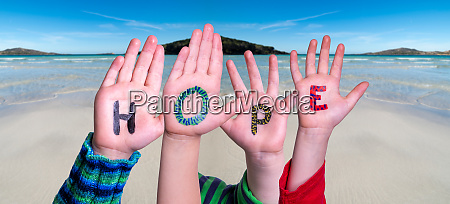 children hands building word hope ocean
